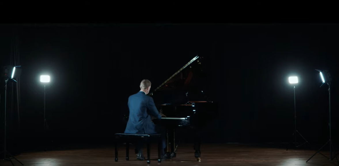 Aaron Playing black piano in blue suit