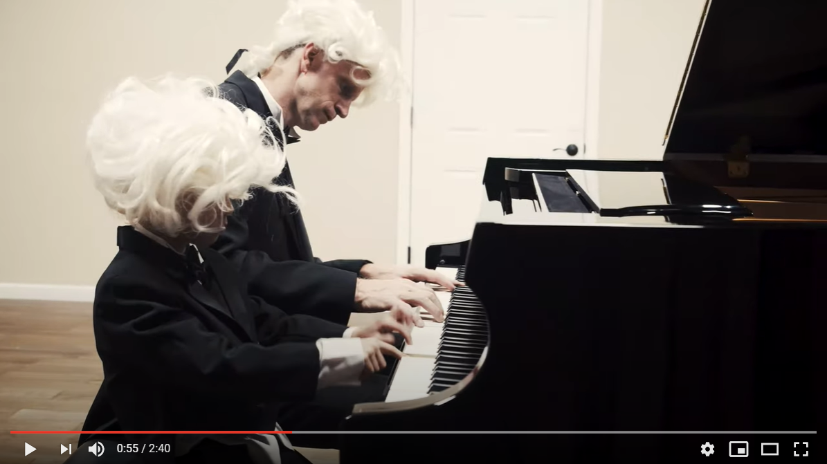 Aaron Ganer and child playing a piano duet