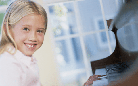 Young girl learning to play the piano.