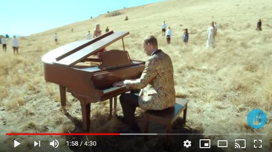 Man playing the piano in an open field