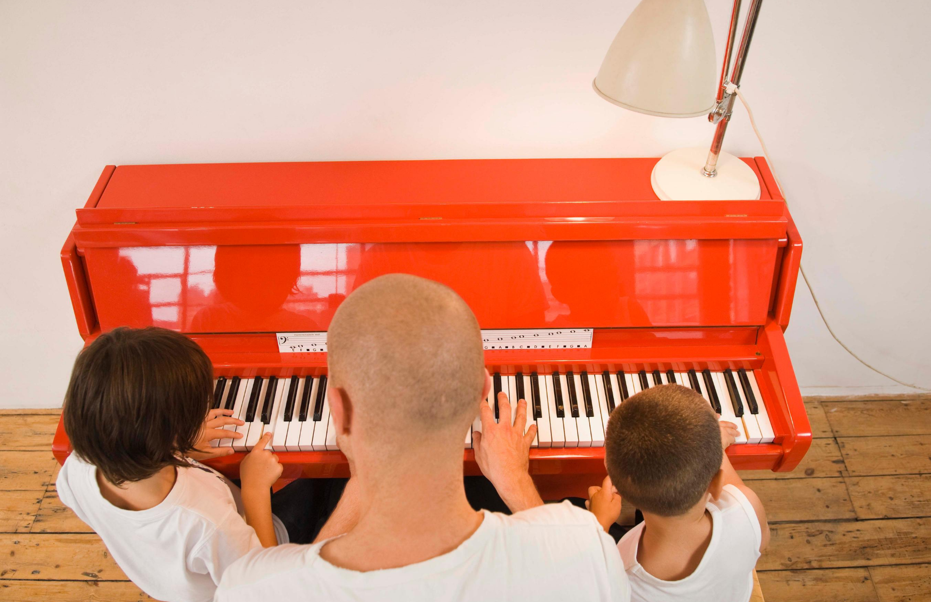 chidren and dad sitting at red piano