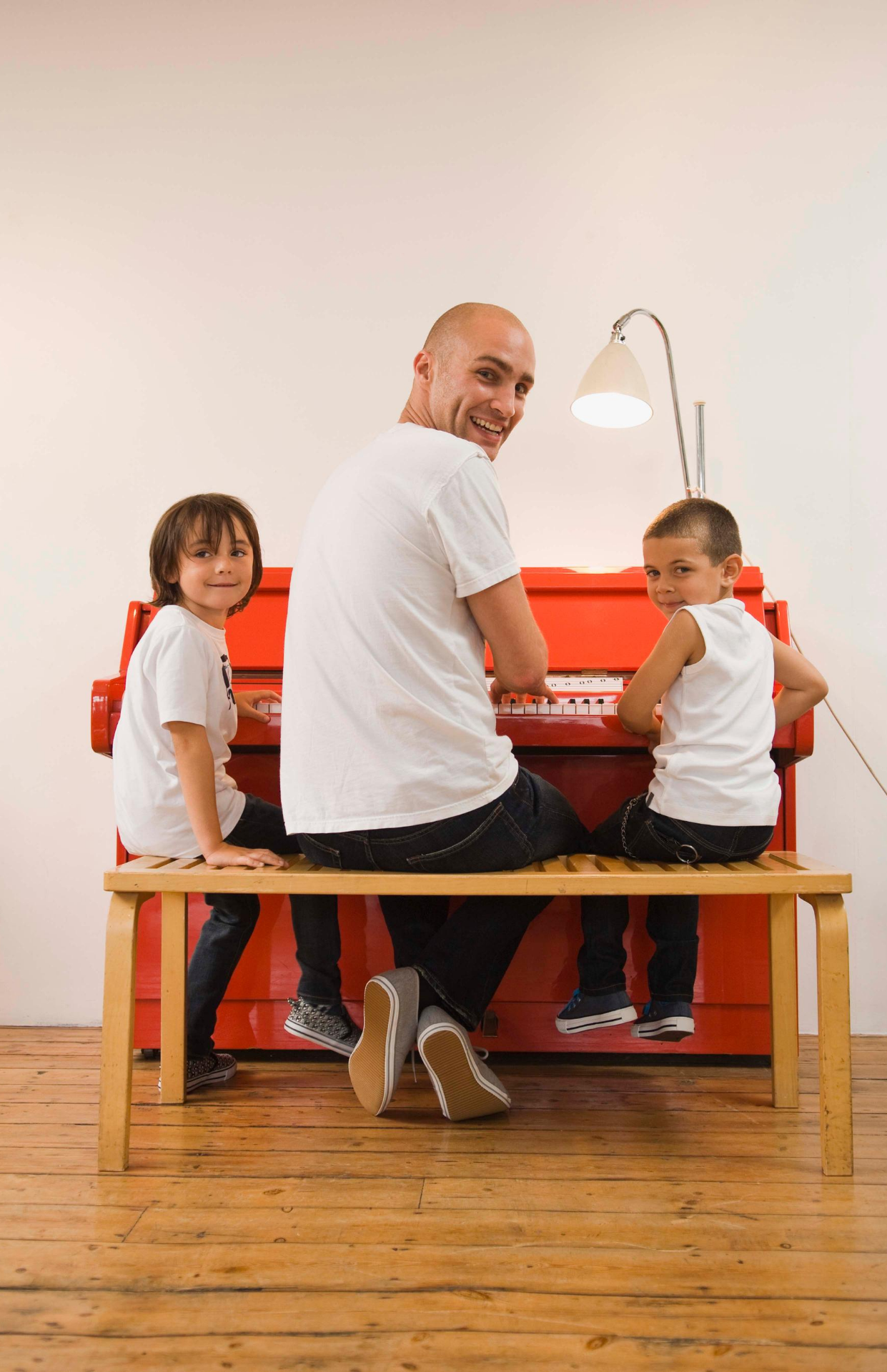 smiling young children with Dad at the piano