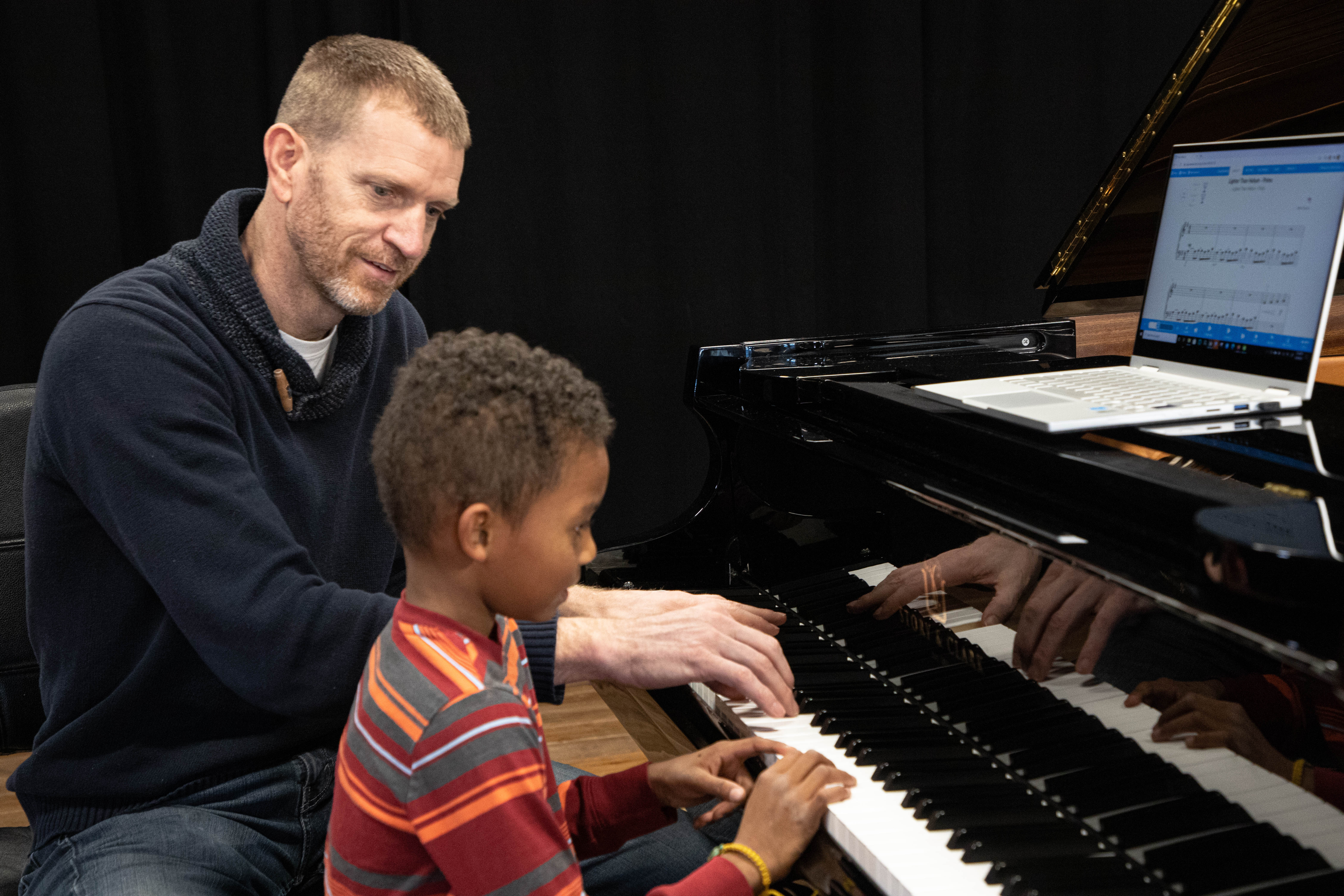 Aaron giving little boy a piano lesson