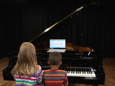 two kids playing black grand piano