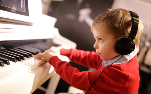 Little boy playing piano with tablet and headphones on