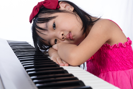 bored girl sitting at piano