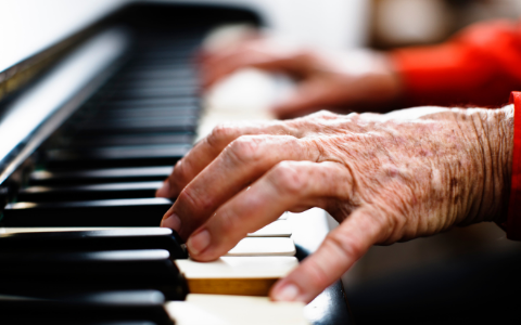 older person hands playing the piano
